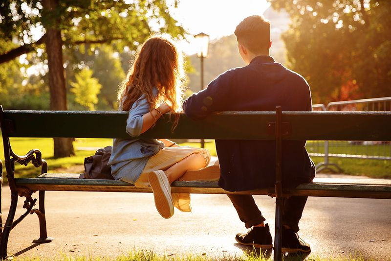 Young couple sitting on a park bench in the Burggarten