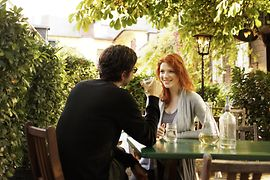 Heuriger Schübel-Auer, outdoor dining area. Young man and woman drinking wine